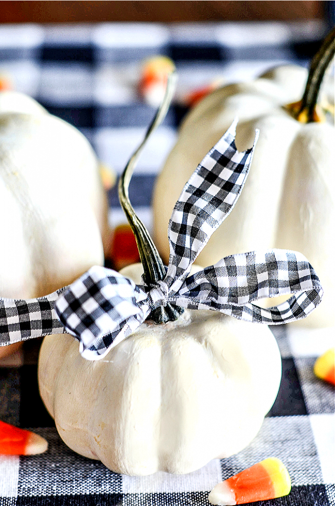 WHITE PAINTED PUMPKINS ON A BLACK AND WHITE CHECKERED CLOTH