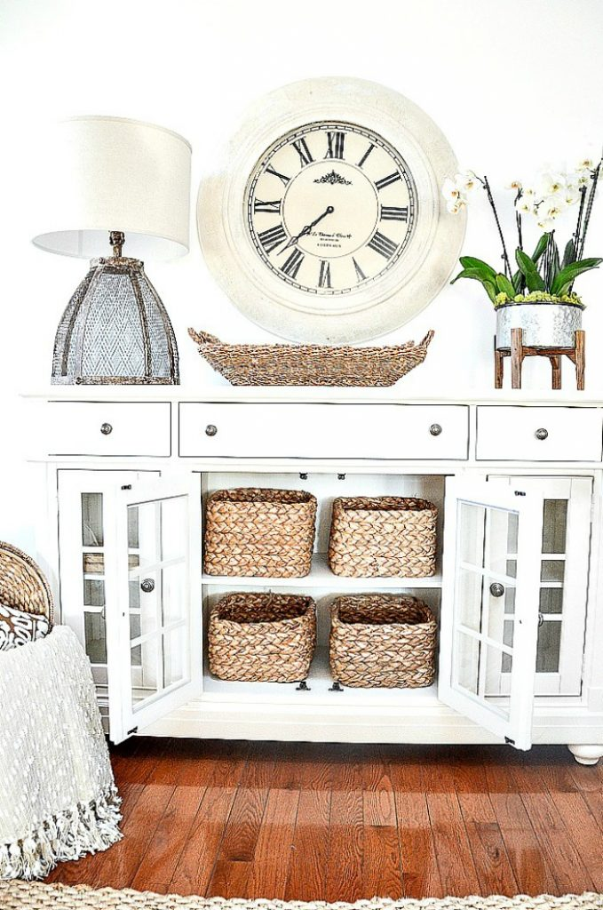 Buffet with a large clock above it. Mixed metal accents.