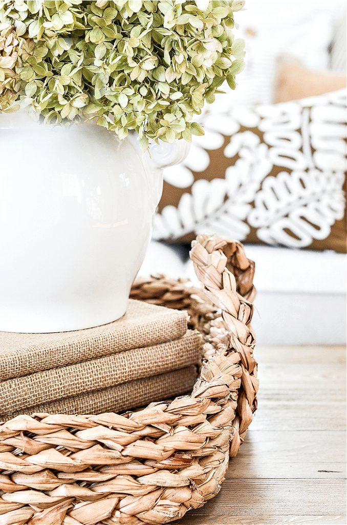 white vase of hydrangeas in a basket on a coffee table