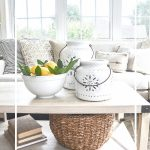 coffee table with white pottery lanterns and a bowl of lemons on it