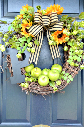 FALL WREATH WITH APPLES AND SUNFLOWERS ON A FRONT DOOR