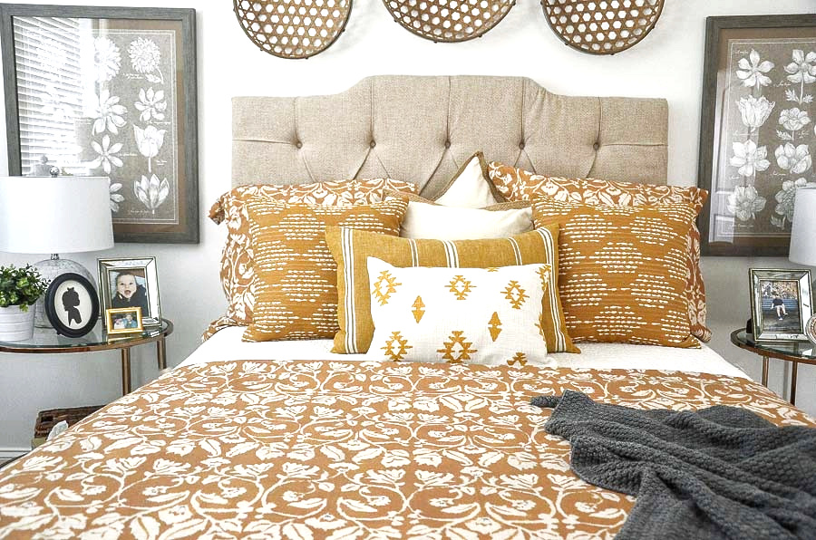master bedroom bed with a neutral upholstered headboard