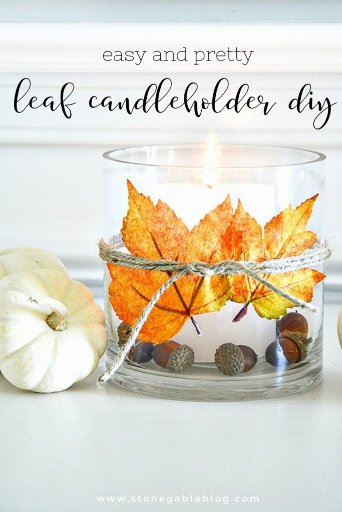 A clear candleholder with a leaf tied with twin around the outside of it