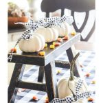 TRIO OF WHITE PAINTED PUMPKINS ON A LITTLE BLACK BENCH