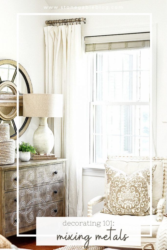A CHEST AND CHAIR AND CURTAINS WITH A MIX OF DECORATIVE METAL ON THEM
