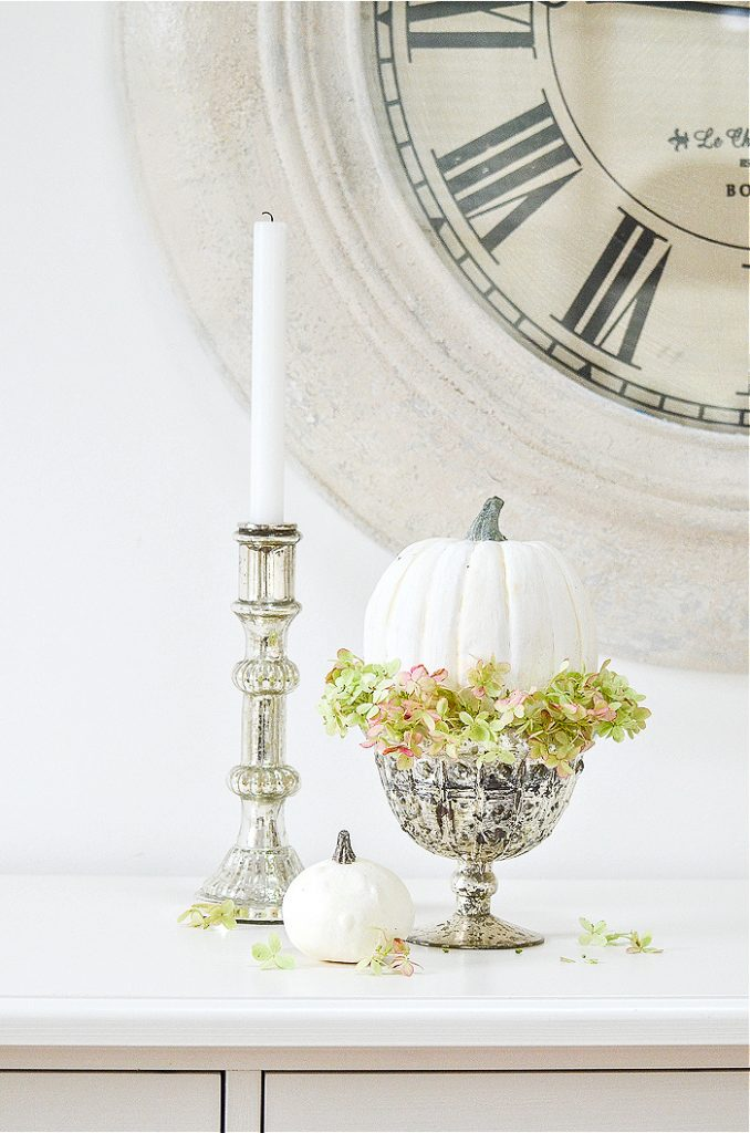 A WHITE PUMPKIN IN A MERCURY GLASS PEDESTAL BOWL WITH A RING OF GREEN AND PINK HYDRANGEAS AROUND IT