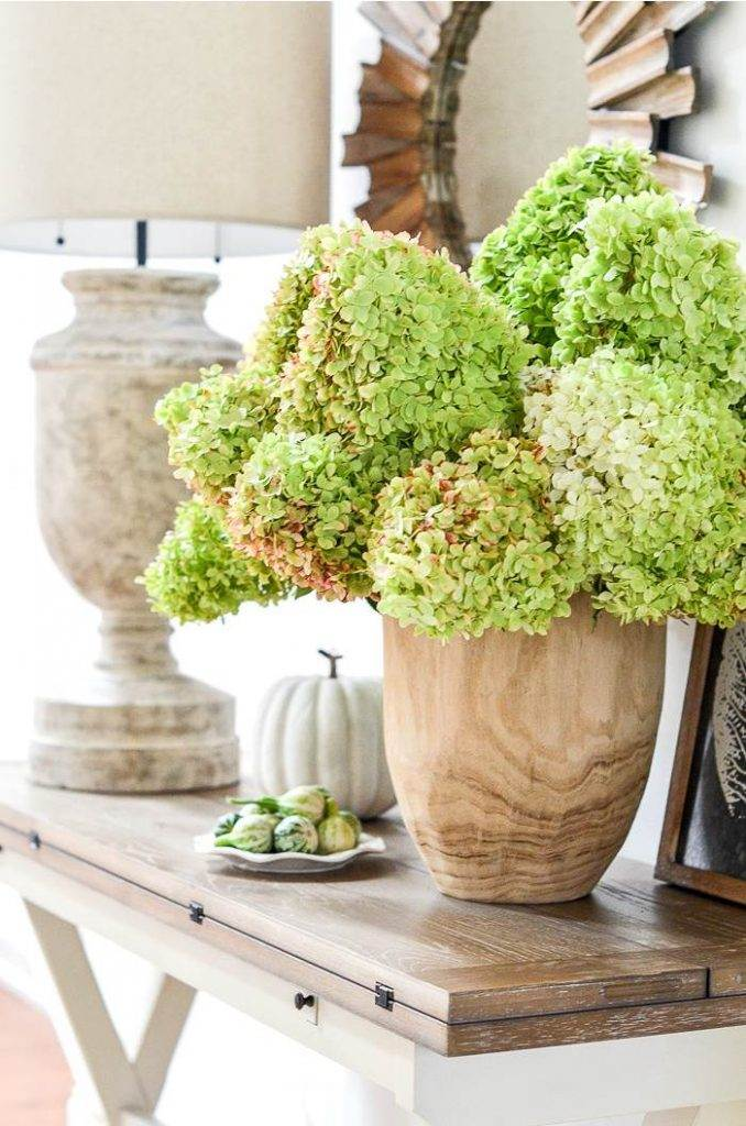 A BIG VASE OF GREEN HYDRANGEAS ON A FOYER TABLE