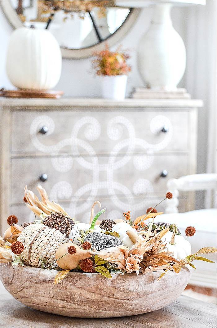 A ROUND WOODEN BOWL FILLED WITH NATURAL FALL ELEMENTS