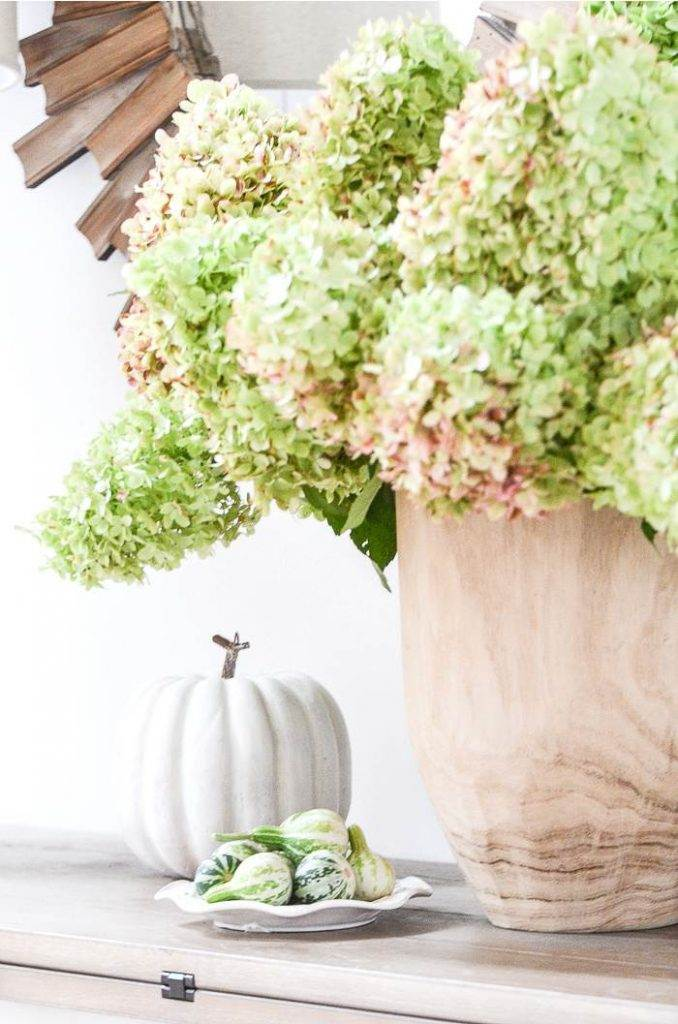 A FOYER TABLE DECORATED WITH HYDRANGEAS, A WHITE PUMPKIN AND A PLATE OF TINY GOURDS