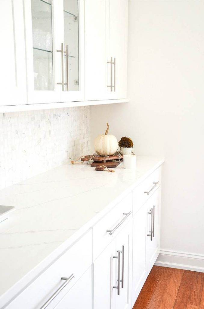A PUMPKIN ON VINTAGE CUTING BOARDS ON A KITCHEN COUNTER