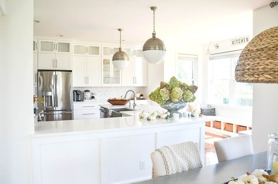 LOOKING INTO A WHITE KITCHEN DECORATED FOR FALL