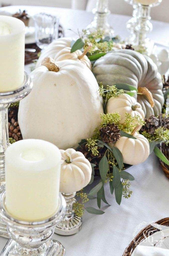 PUMPKINS AND SEEDED EUCALYPTUS AND ACORNS DECORATING A TABLE