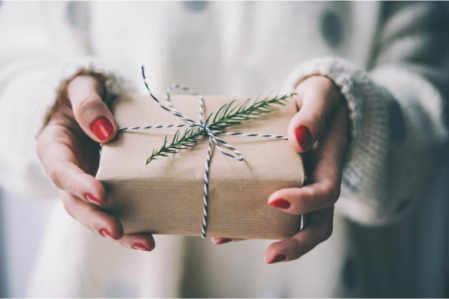 A WRAPPED CHRISTMAS PACKAGE WITH A SPRIG OF EVERGREEN TUCKED UNDER THE TWINE WRAP
