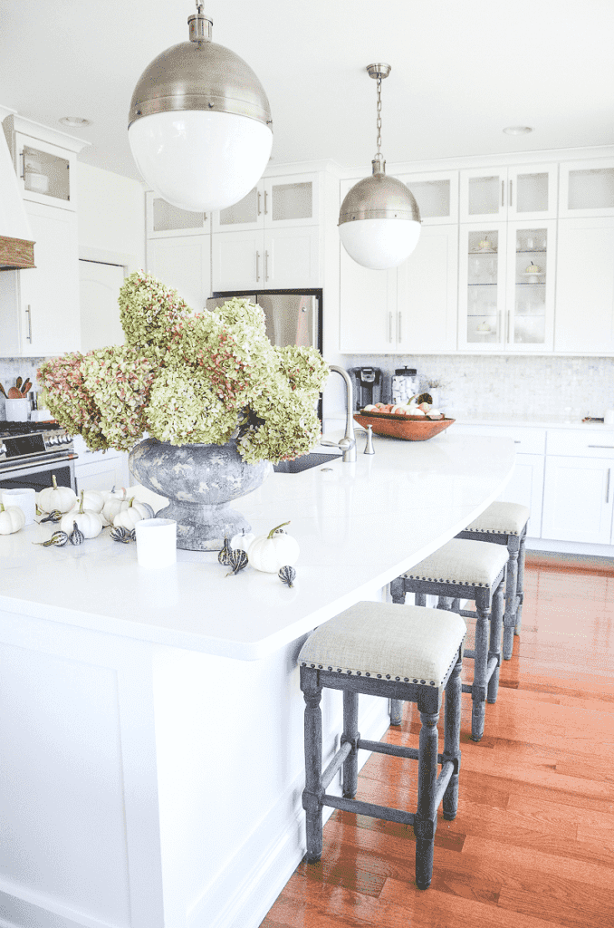 a big urn of green hydrangeas sitting on a kitchen counter