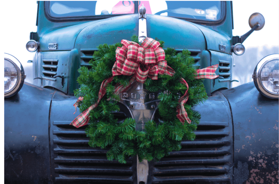 A BLUE TRUCK WITH A WREATH ON THE GRILL