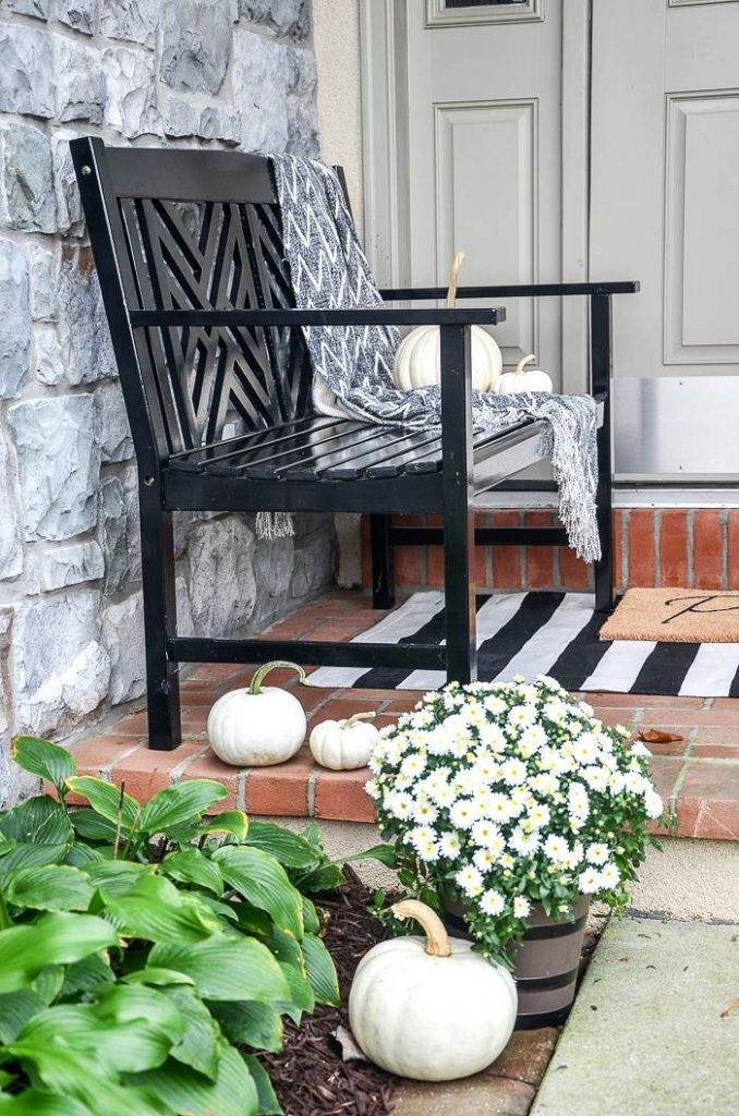 A BLACK BENCH ON A FRONT PORCH DECORATED FOR FALL