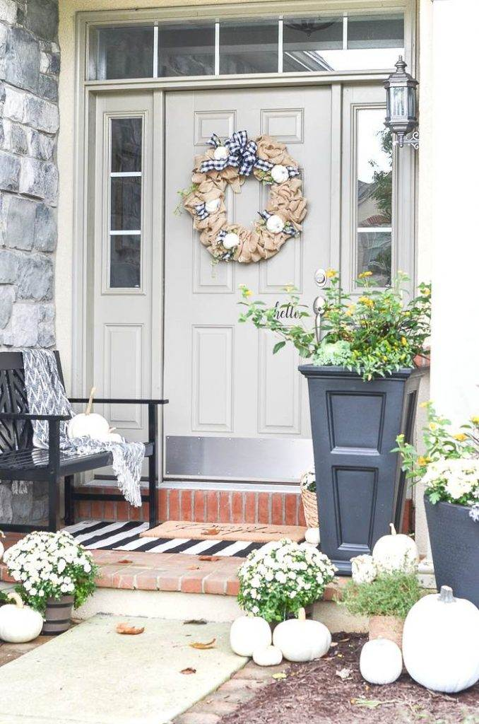 A FRONT DOOR AND SMALL PORCH DECORATED FOR FALL