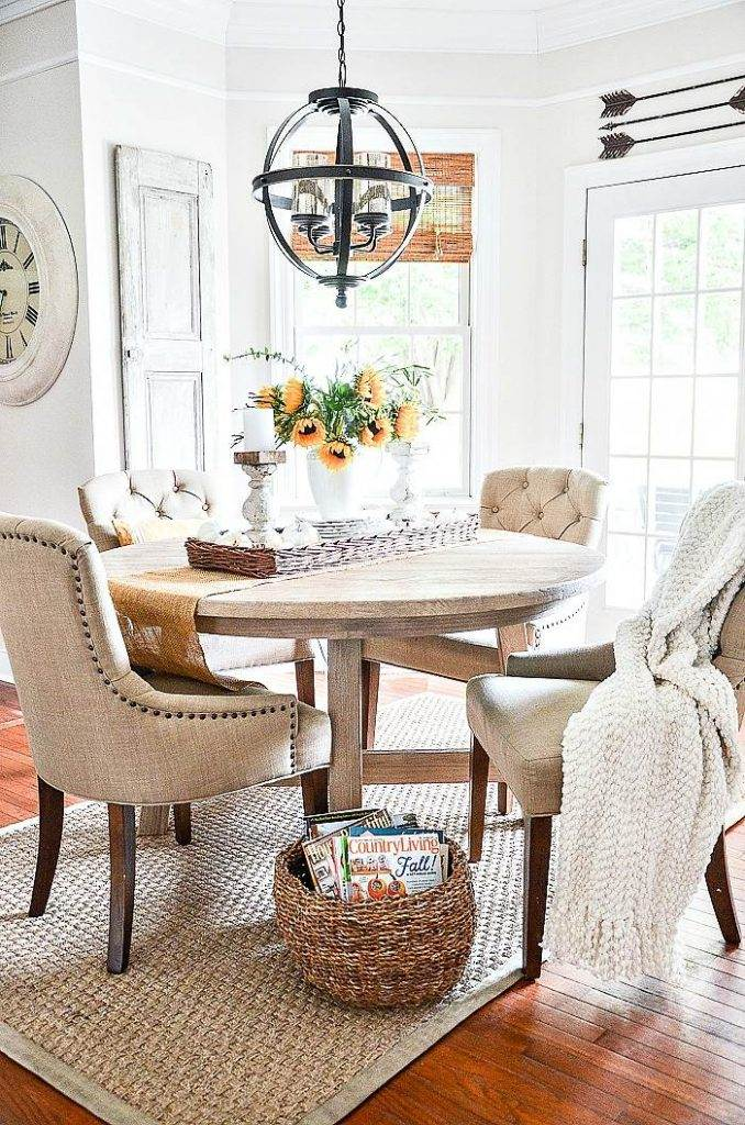 FOUR TAN UPHOLSTERED CHAIRS AROUND A ROUND TABLE