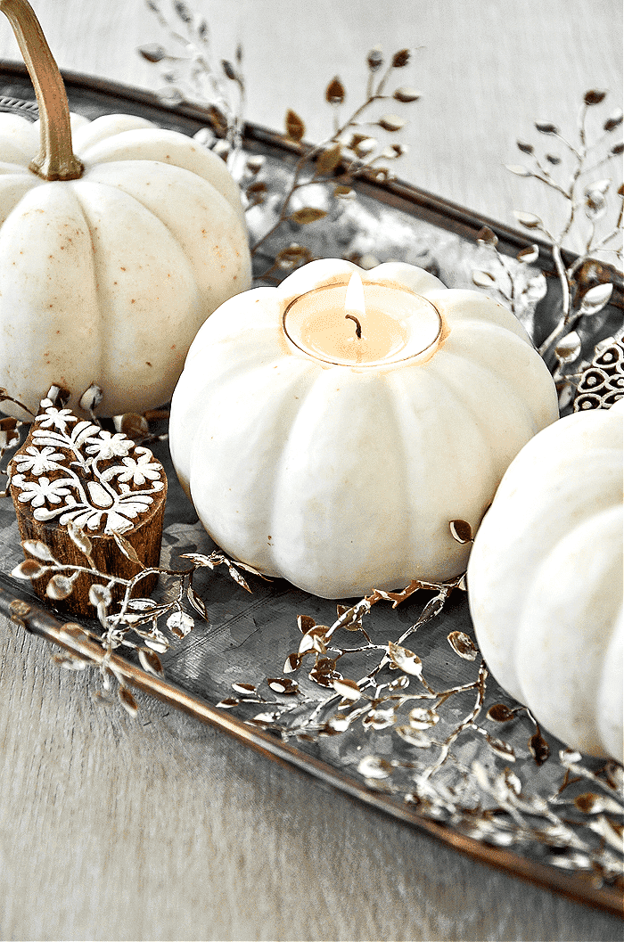 COLLAGE PIN OF A WHITE PUMPKIN WITH A CANDLE IN IT