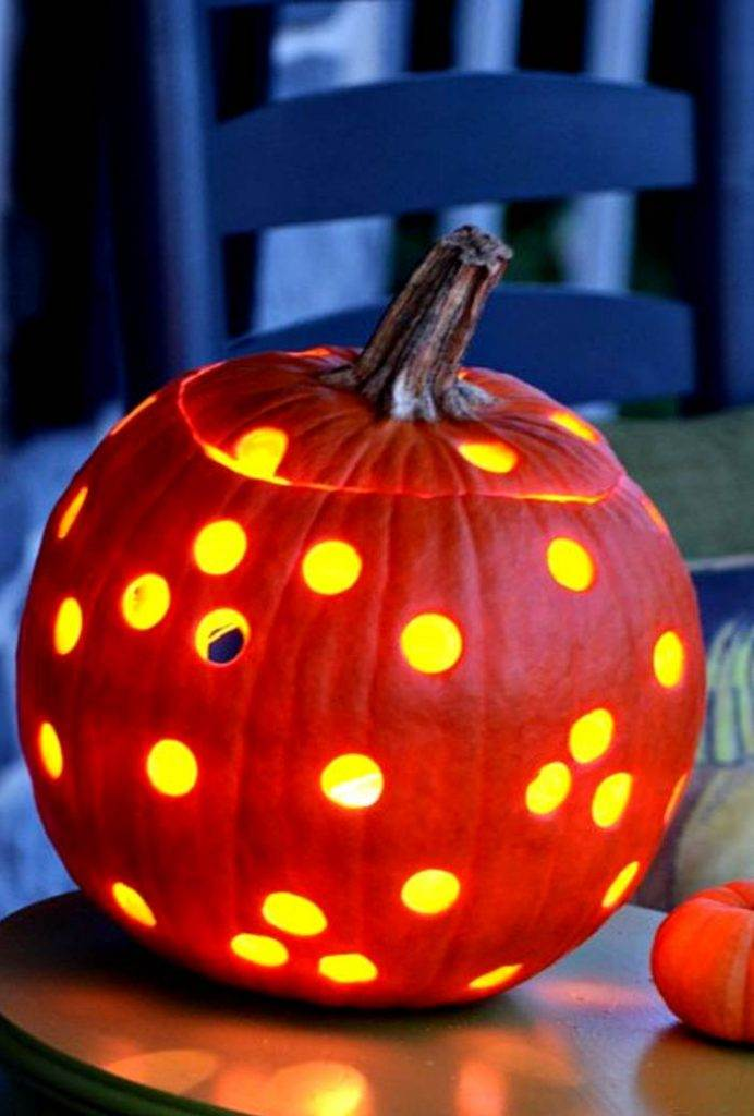 carved pumpkin jack- o - lantern with lots of holes