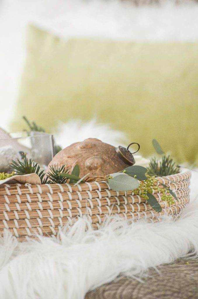 christmas arrangement in a basket on a bed