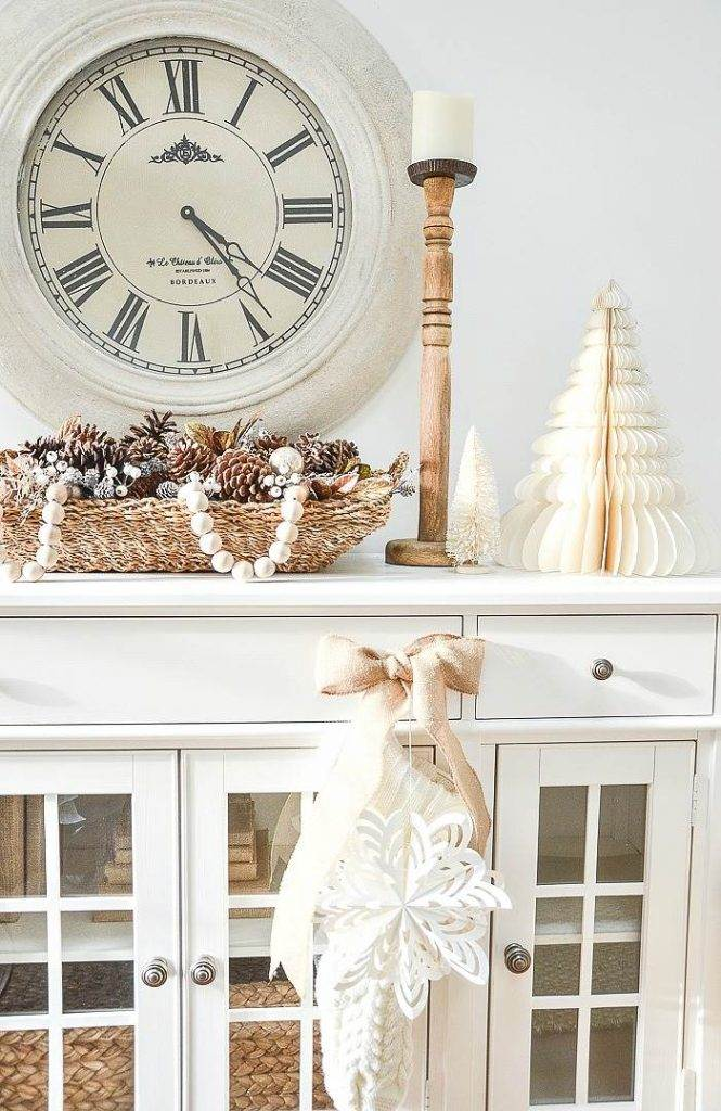CHRISTMAS ARRANGEMENT OF PINECONES ON A WHITE BUFFET