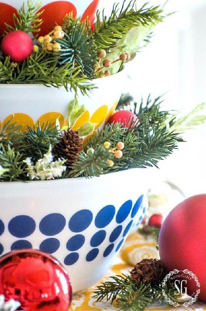 BOWLS STACKED UPON ONE ANOTHER AND FILLED WITH GREENS AND ORNAMENTS