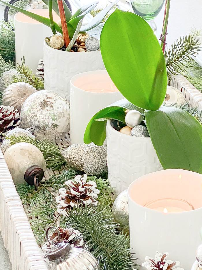 GREENS, ORNAMENTS AND PINECONE IN A TABLE CENTERPIECE