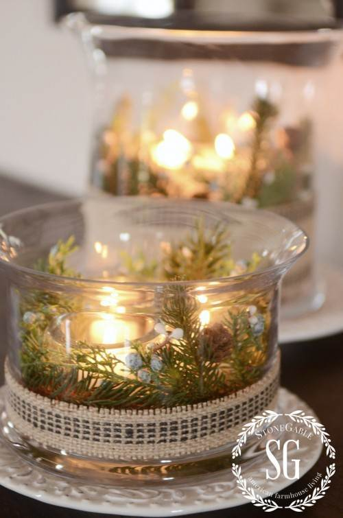 CANDLES IN A LARGER GLASS CONTAINER WITH GREENS
