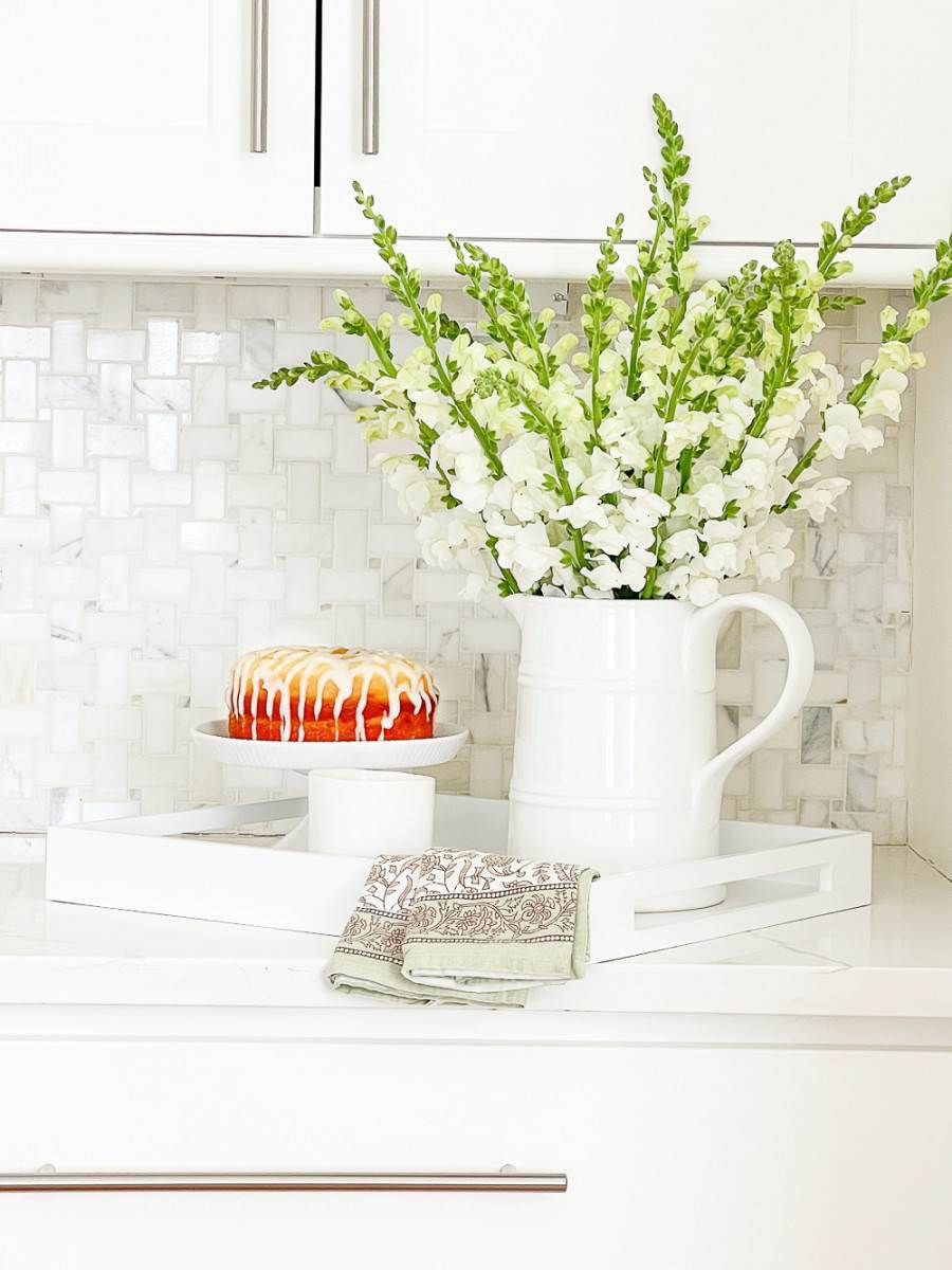 PITCHER OF SNAPDRAGONS ON A KITCHEN COUNTER