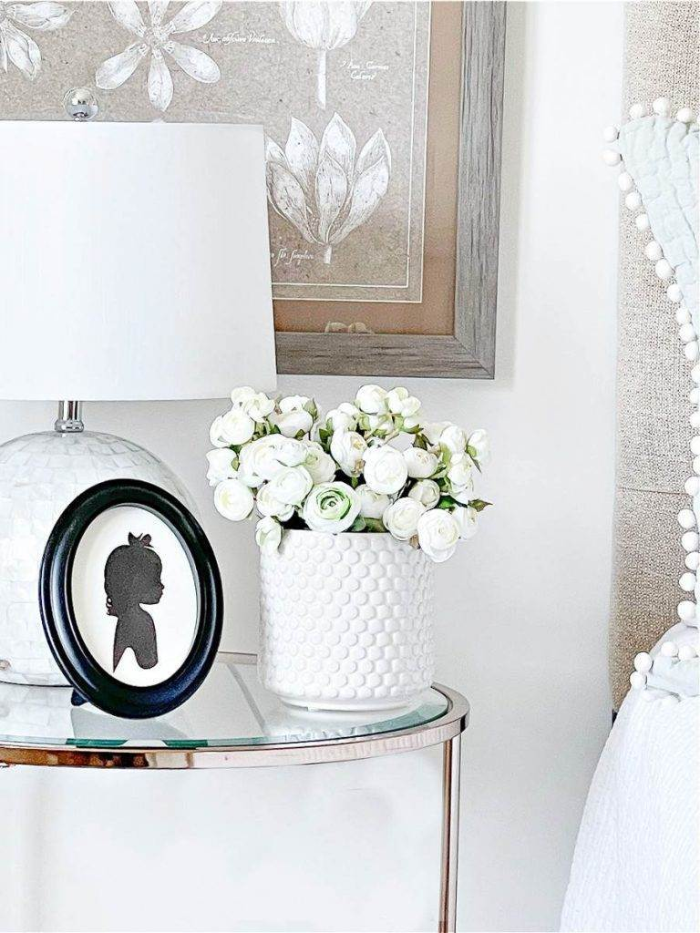 NIGHT STAND IN BEDROOM WITH WHITE FLOWERS ON IT