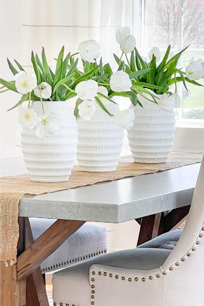 THREE VASES OF TULIPS ON A TABLE