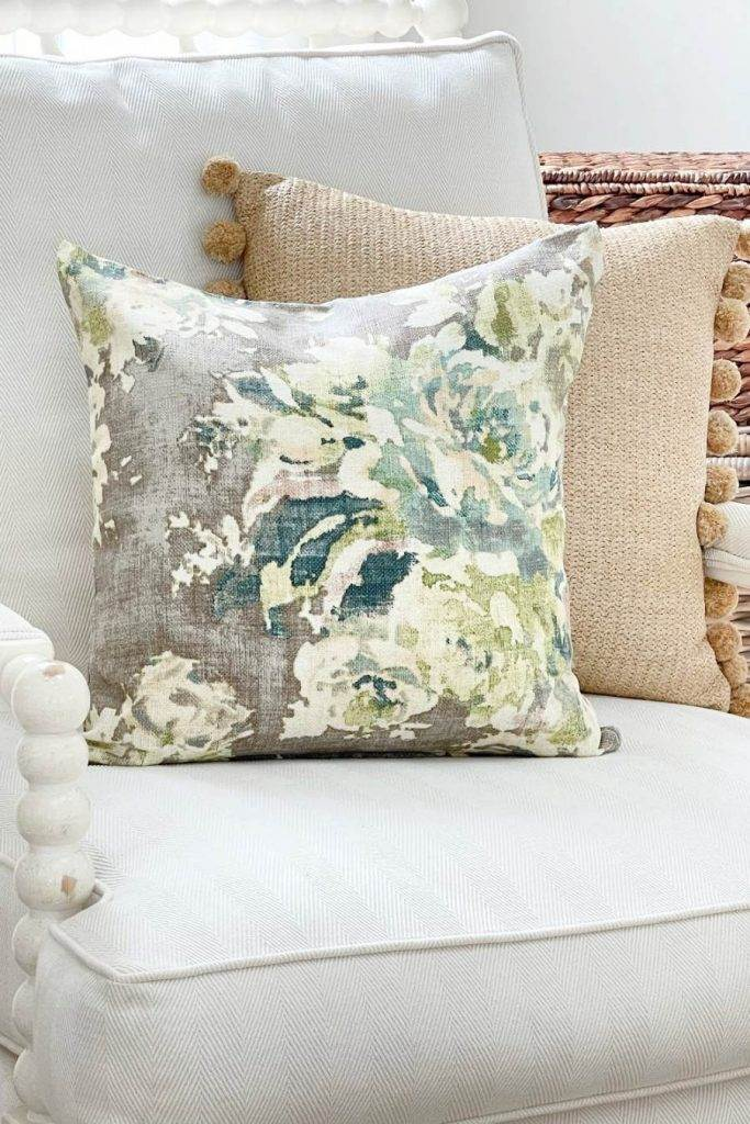 A DUO OF PRETTY PILLOWS ON A WHITE CHAIR