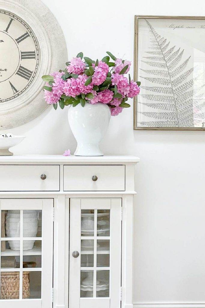 WHITE BUFFET WITH A VASE OF PURPLE FLOWERS