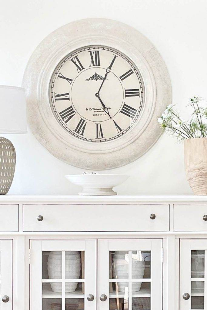 A WHITE BUFFET WITH A BIG CLOCK ABOVE IT