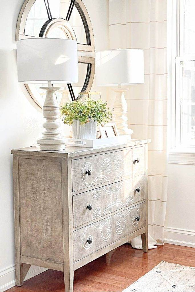 PRETTY CHEST WITH A MIRROR ABOVE IT IN A LIVING ROOM