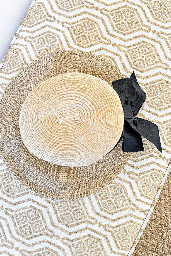 HAT ON AN UPHOLSTERED BENCH