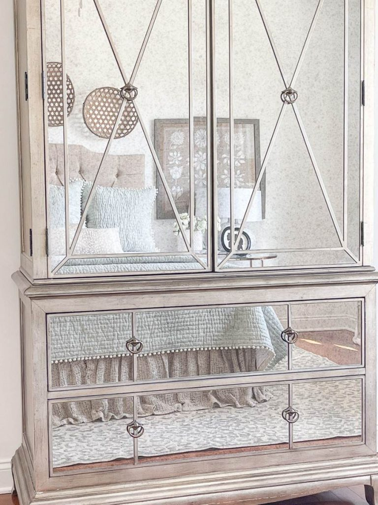 MIRRORED ARMOIRE WITH A BED REFLECTED IN IT