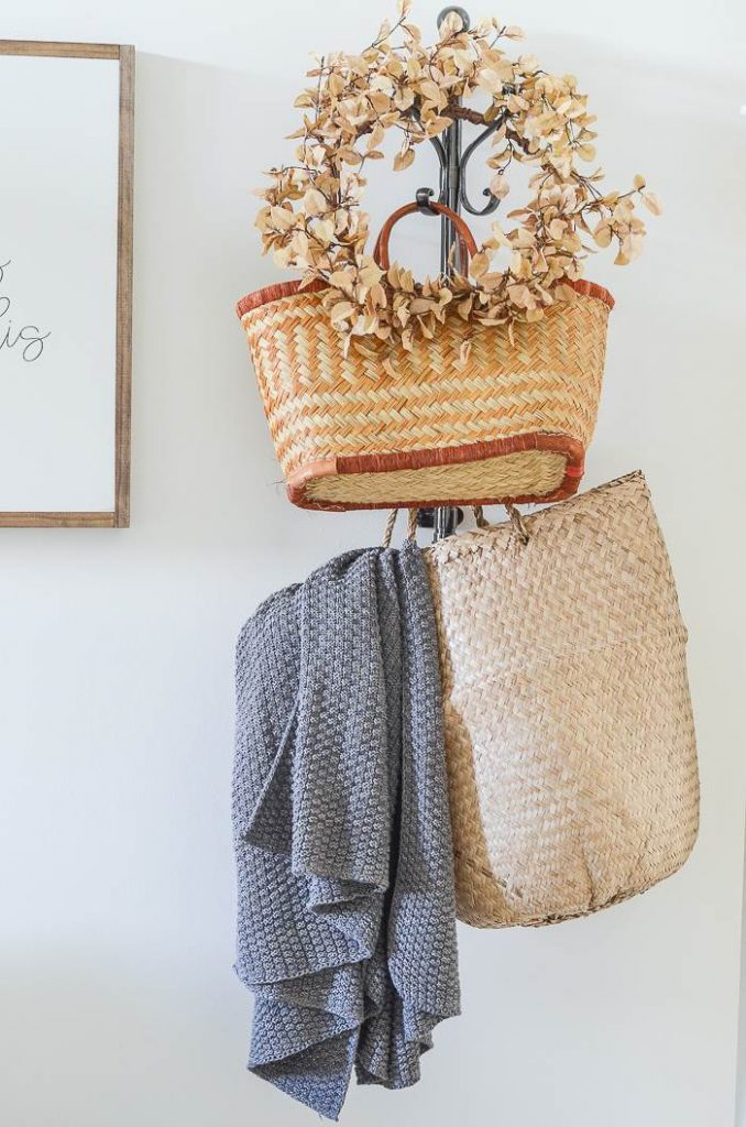 coat rack with baskets and a throw and wreath