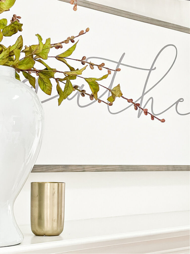 close-up of branches, a candle and a gather sign on the wall behind the mantel